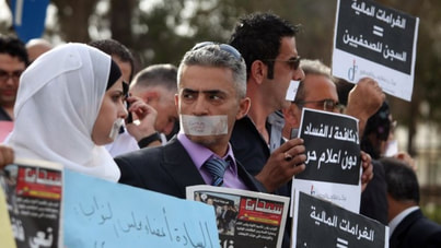 Photograph of protesters with tape over their mouths holding signs written in Arabic